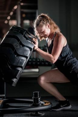 Day Night Sports Frau beimTraining, Heben eines Reifens