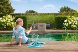 Gartenfotografie Frau spritzt Wasser mit Fuss