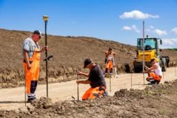 4 Bauarbeiter Abmessungen auf einer Baustelle