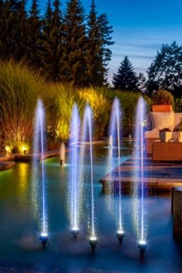 Gartenfotografie Garten mit Wasserspiel Wasserfontänen beleuchtet