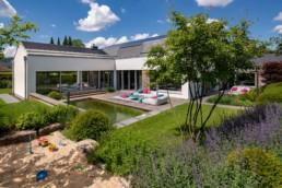 Modernes Haus mit Garten und kleinem Sandkasten Garten und Pool beleuchtet in der blauen Stunde fotografiert von Thorsten Scherz Fotografie