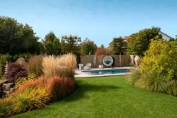Gartenfotografie Garten mit Pool Stauden Herbst